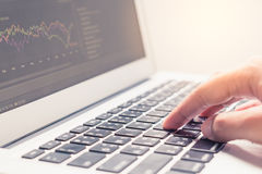 Woman hand typing on laptop keyboard with graph on screen Stock Photo