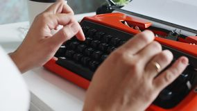Woman hand typing on red vintage typewriter. Back view of woman hand typing on red vintage typewriter stock footage