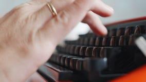 Woman hand typing on red vintage typewriter. Side view of woman hand typing on red vintage typewriter stock video
