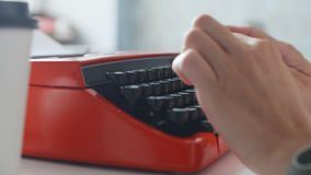 Woman hand typing on red vintage typewriter. Side view of woman hand typing on red vintage typewriter stock video footage