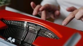 Woman hand typing on red vintage typewriter. Slow motion shot of woman hand typing on red vintage typewriter stock footage