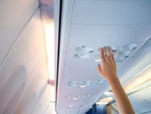 Woman hand up to adjust console panel at the air conditioner above the seat in airplane stock image