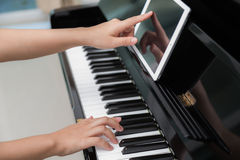 Woman hand use tablet and  playing piano Stock Photo