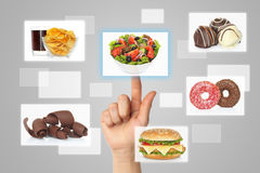 Woman hand uses touch screen interface with food Royalty Free Stock Image