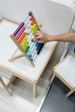 Woman hand using Abacus toy on kid study table royalty free stock photos