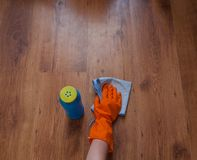 A woman hand Using blue rags wipe the wooden floor.  Stock Photo