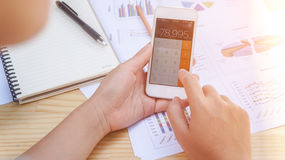 Woman hand  using calculator and calculate about cost at home office. Royalty Free Stock Photo