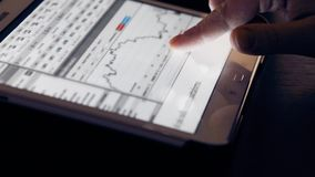 Woman hand using finger for touching tablet computer pc touch screen on financial chart for business stock footage