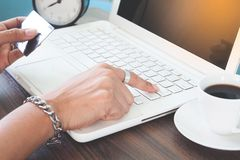 Woman hand using laptop computer and holding credit card Stock Photography