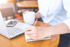 Woman hand using laptop and writing in notepad with a pen. Stock Image