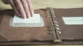 Woman hand using light brown leather case elegant daily planner note pad book habit tracker on wooden table in close up. Close up shot of elegant light brown stock video