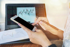 Woman hand using smart phone while analyzing financial and stock graph on her notebook. In background Royalty Free Stock Photo