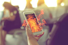 Woman hand Using a Smart Phone with flame fire. Royalty Free Stock Photos