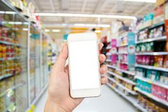 Woman hand using smart phone on Supermarket blur background stock images