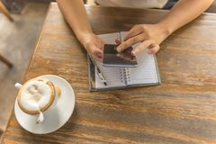 Woman hand using smartphone in the coffee shop stock photo