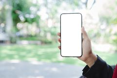 Woman hand using smartphone mockup and blurred green garden background. Blank screen mobile phone for graphic display montage royalty free stock photo