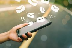Woman hand using smartphone to send email for business on nature bokeh background. Woman hand using smartphone to send and recieve email for business on road stock illustration