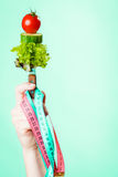 Woman hand with vegetarian food and measuring tapes. Diet and weight loss concept. Dietician woman hand with vegetarian food and colorful measuring tapes on Stock Photo