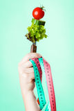 Woman hand with vegetarian food and measuring tapes. Diet and weight loss concept. Dietician woman hand with vegetarian food and colorful measuring tapes on Royalty Free Stock Photo