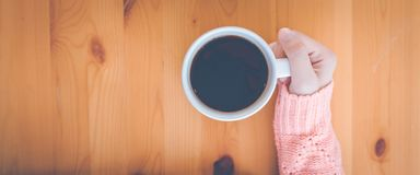 Woman hand in warm pink sweater holding a cup of coffee.Web banner royalty free stock photography