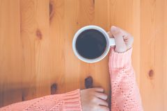 Woman hand in warm pink sweater holding a cup of coffee stock photography