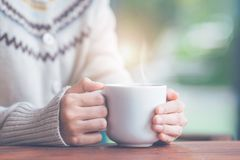 Woman hand in warm sweater holding a cup of coffee. stock photography