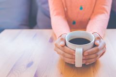 Woman hand in warm sweater holding a cup of coffee stock photos