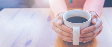 Woman hand in warm sweater holding a cup of coffee.Web banner stock photo