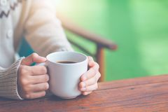 Woman hand in warm sweater holding a cup of coffee. royalty free stock photo