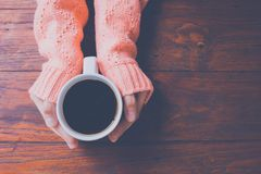 Woman hand in warm sweater holding a cup of coffee on a wooden t stock photography