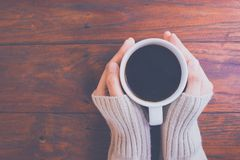 Woman hand in warm sweater holding a cup of coffee on a wooden t stock photos