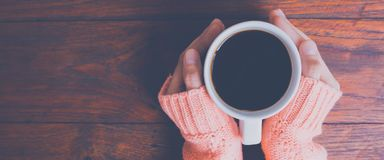 Woman hand in warm sweater holding a cup of coffee on a wooden t royalty free stock photography