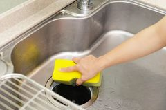 Woman wash the kitchen sink. Woman hand wash the kitchen sink royalty free stock image