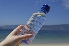 Woman hand with a water bottle on the beach Stock Photo