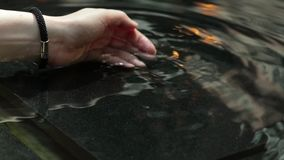 Woman hand with water splash, backlit by the evening sun. Beautiful tanned hands of a young woman. Woman hand with water splash, back lit by the evening sun stock video footage