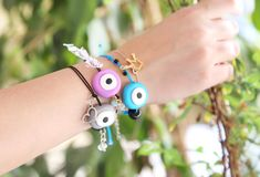 Woman hand wearing colorful evil eye bracelets Stock Images