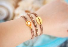 Woman hand wearing stylish brown bracelets with evil eye and cross - macrame bracelets royalty free stock photo