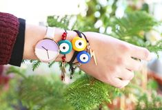 Woman hand wearing stylish evil eye bracelets - greek jewelry advertisement Stock Photo
