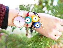 Woman hand wearing stylish evil eye bracelets Stock Image