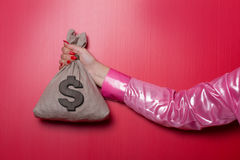 Woman Hand Whit Money Bag. Money bag with dollar sign on red background Royalty Free Stock Images