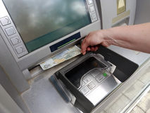 Woman hand withdrawing money from outdoor bank ATM Royalty Free Stock Image