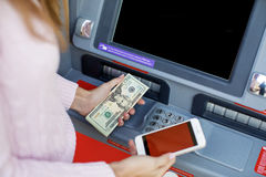 Woman hand withdrawing money from outdoor bank ATM Stock Image