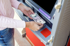 Woman hand withdrawing money from outdoor bank ATM Royalty Free Stock Photography