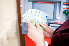 Woman hand withdrawing money from outdoor bank ATM Royalty Free Stock Photo