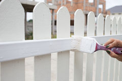 Woman hand worker painting white fence Stock Photos