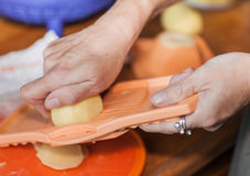 Woman hand working on a potato grater Royalty Free Stock Image