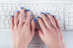 Woman hand working on white laptop keyboard stock photography