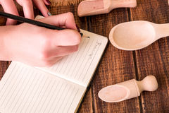 Woman hand write a recipe in cookbook. Book for recipe around utensils on wooden background. Woman hand write a recipe in cookbook. Book for recipe around Royalty Free Stock Images