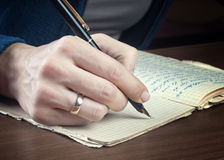 Woman hand writes on a paper Royalty Free Stock Photography