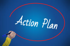 Woman hand writing action plan with marker. On blue background Royalty Free Stock Photography